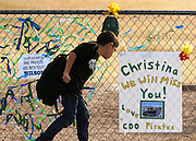 A student at Mesa Verde Elementary school looks at a memorial at his school to killed classmate Christina Taylor Green after school let out in Tucson, Arizona January 10, 2011.  REUTERS/Rick Wilking (UNITED STATES)