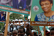 Liberian presidential candidate Ellen Johnson Sirleaf (at R on truck in background, smiling) looks over a crowd of supporters as she parades in Monrovia, Liberia.