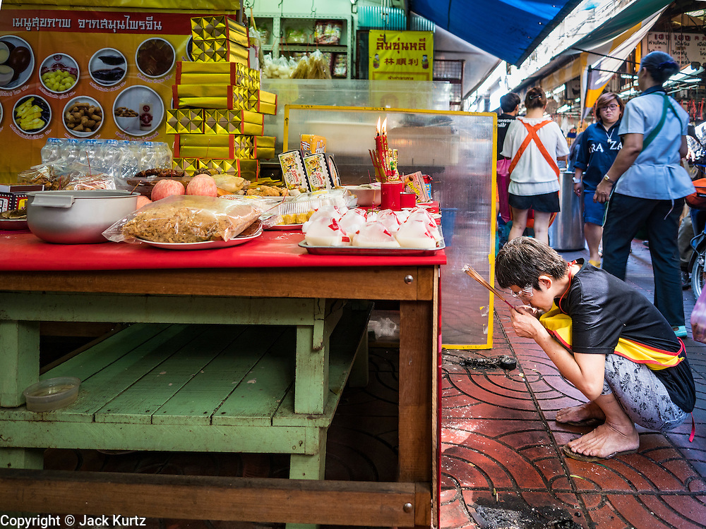 27 JANUARY 2017 - BANGKOK, THAILAND: A woman prays at homemade family altar in a market in Bangkok's Chinatown on Chinese New Year in Bangkok. 2017 is the Year of the Rooster in the Chinese zodiac. This year's Lunar New Year festivities in Bangkok were toned down because many people are still mourning the death Bhumibol Adulyadej, the Late King of Thailand, who died on Oct 13, 2016. Chinese New Year is widely celebrated in Thailand, because ethnic Chinese are about 15% of the Thai population.       PHOTO BY JACK KURTZ