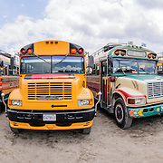 Panorama of a variety of brightly painted old American school buses converted into chicken buses converge in the lot behind the city market.
