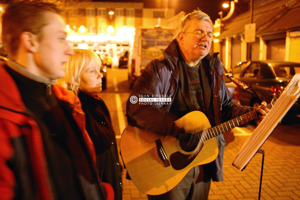 Man playing the guitar and small group of people singing in the streets of Nottingham at night,