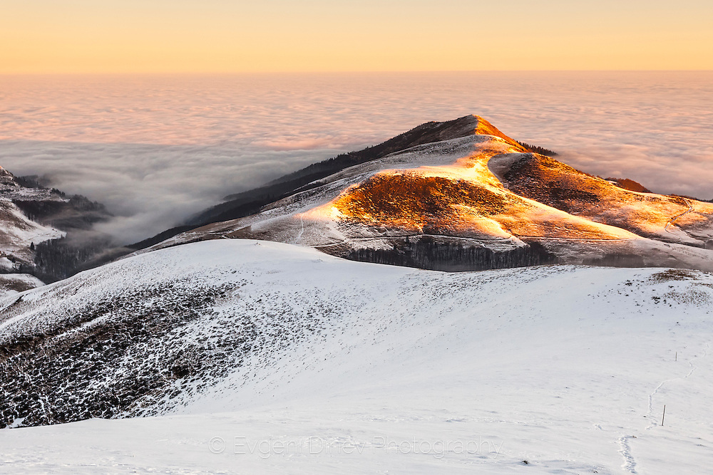 Snowy mountain ridge above the clouds.