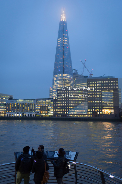 Visitors to London admire a view over the Thames river and the Shard skyscraper on a winter's afternoon, on 23rd November 2018, in London, England.