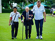 "11 NOVEMBER 2018 - KANCHANABURI, KANCHANABURI, THAILAND: ARCHIE DUNLOP (center), 95 years old, a British veteran of World War II, is helped into the Rememberance Day ceremony at the Kanchanaburi War Cemetery in Kanchanaburi, Thailand. Kanchanaburi is the location of the infamous ""Bridge On the River Kwai"" and was known for the ""Death Railway"" built by Japan during World War II using allied, principally British, Australian and Dutch, prisoners of war as slave labor. There are 6,982 people buried in the cemetery, including 5,000 Commonwealth soldiers and 1,800 Dutch soldiers. November 11, 2018 marked the 100th anniversary of the end of World War I, celebrated as Rememberance Day in the UK and the Commonwealth and Veterans' Day in the US.    PHOTO BY JACK KURTZ"