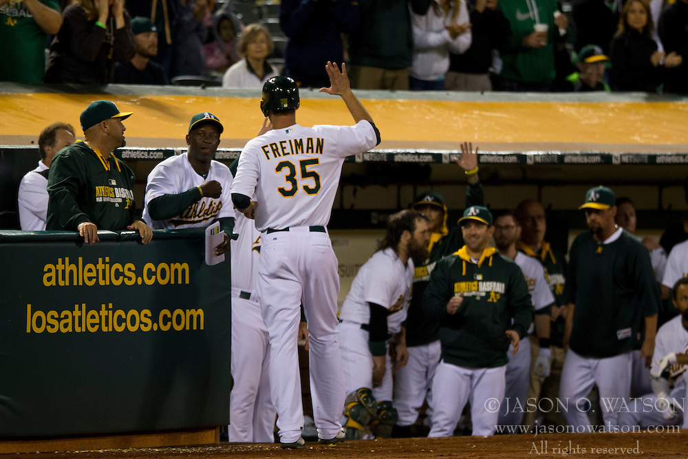 OAKLAND, CA - JULY 05:  Nate Freiman #35 of the Oakland Athletics is congratulated by teammates in the dugout after scoring a run against the Toronto Blue Jays during the eighth inning at O.co Coliseum on July 5, 2014 in Oakland, California. The Oakland Athletics defeated the Toronto Blue Jays 5-1.  (Photo by Jason O. Watson/Getty Images) *** Local Caption *** Nate Freiman