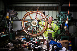 "© Licensed to London News Pictures. 04/05/2016. Birkenhead UK. Picture shows former Tug man & volunteer Phil Janion working on the Daniel Adamson's wheel at the Canada Dock volunteer workshop. The Daniel Adamson steam boat has been bought back to operational service after a £5M restoration. The coal fired steam tug is the last surviving steam powered tug built on the Mersey and is believed to be the oldest operational Mersey built ship in the world. The ""Danny"" (originally named the Ralph Brocklebank) was built at Camel Laird ship yard in Birkenhead & launched in 1903. She worked the canal's & carried passengers across the Mersey & during WW1 had a stint working for the Royal Navy in Liverpool. The ""Danny"" was refitted in the 30's in an art deco style. Withdrawn from service in 1984 by 2014 she was due for scrapping until Mersey tug skipper Dan Cross bought her for £1 and the campaign to save her was underway. Photo credit: Andrew McCaren/LNP ** More information available here http://tinyurl.com/jsucxaq **"