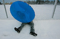 Tommy Spengler, 12, of Rockland Massachusetts, hides from the wind behind his snow tube while sledding in his home town on December 27, 2010.  The area was hit by a blizzard which dumped over a foot and a half of snow in other parts of the state and caused coastal flooding.   UPI/Matthew Healey