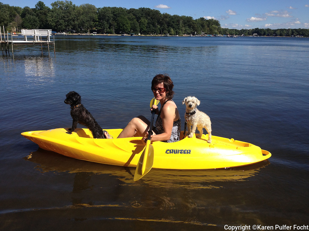 Cindy Rogan, takes her dogs Patsy and Loretta for a ride in her kayak  while relaxing on vacation in Michigan.