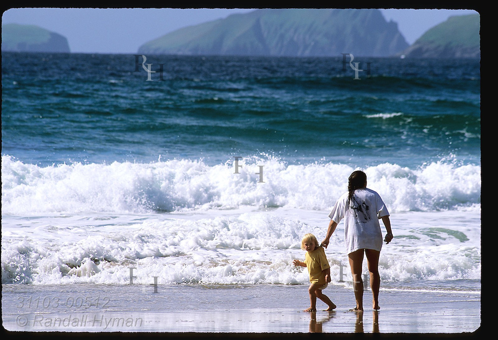 Mom & diaper girl wet toes in the chilly North Atlantic surf of Coumeenole Beach with Blasket Islands in distance; Dingle, Ireland.