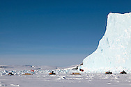Canadian Rangers ride snowmobiles on icepack next to an adrift iceberg off Gascoyne Inlet (Devon Island, Nunavut) during Nunalivut 2012 sovereignty exercise by Canadian Forces in arctic Canada. Rangers are non-combat, part-time reserve auxiliaries that mix local volunteers, here Inuits, and professional military acting as eyes and ears in the most remote areas of northern Canada. 17 April 2012.