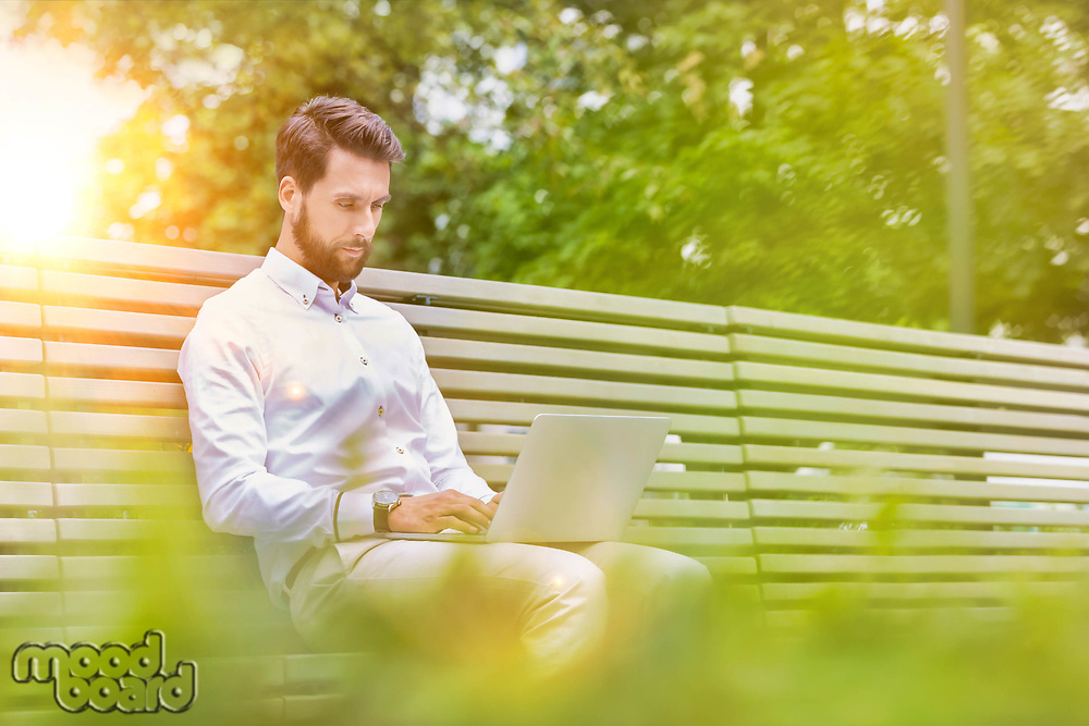 Portrait of young attractive businessman sitting on bench while working on his laptop