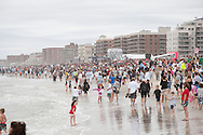 20110911 - Long Beach , NY - Supporters watch as surfers, made up of police, fire fighters, military, and local and pro surfers form a circle during a paddle out in remembrance of 9/11 as part of a beach mass and ecumenical service at National Boulevard Beach.  .Photo by Isabel Slepoy / LI Herald