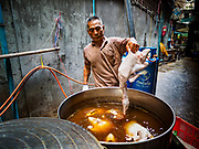 03 FEBRUARY 2019 - BANGKOK, THAILAND: A workers drops a duck into a stewing vat in Bangkok's Chinatown district. The ducks were being stewed for Chinese New Year's banquets. Chinese New Year celebrations in Bangkok start on February 4, 2019. The coming year will be the Year of the Pig in the Chinese zodiac. About 14% of Thais are of Chinese ancestry and Lunar New Year, also called Chinese New Year or Tet is widely celebrated in Chinese communities in Thailand.        PHOTO BY JACK KURTZ
