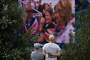 Two spectators watch a large tv screen coverage during the London 2012 Olympics. Spectators pass by as the team members celebrate with emotional hugs in their winning boat a few miles away in west London. This land was transformed to become a 2.5 Sq Km sporting complex, once industrial businesses and now the venue of eight venues including the main arena, Aquatics Centre and Velodrome plus the athletes' Olympic Village. After the Olympics, the park is to be known as Queen Elizabeth Olympic Park.
