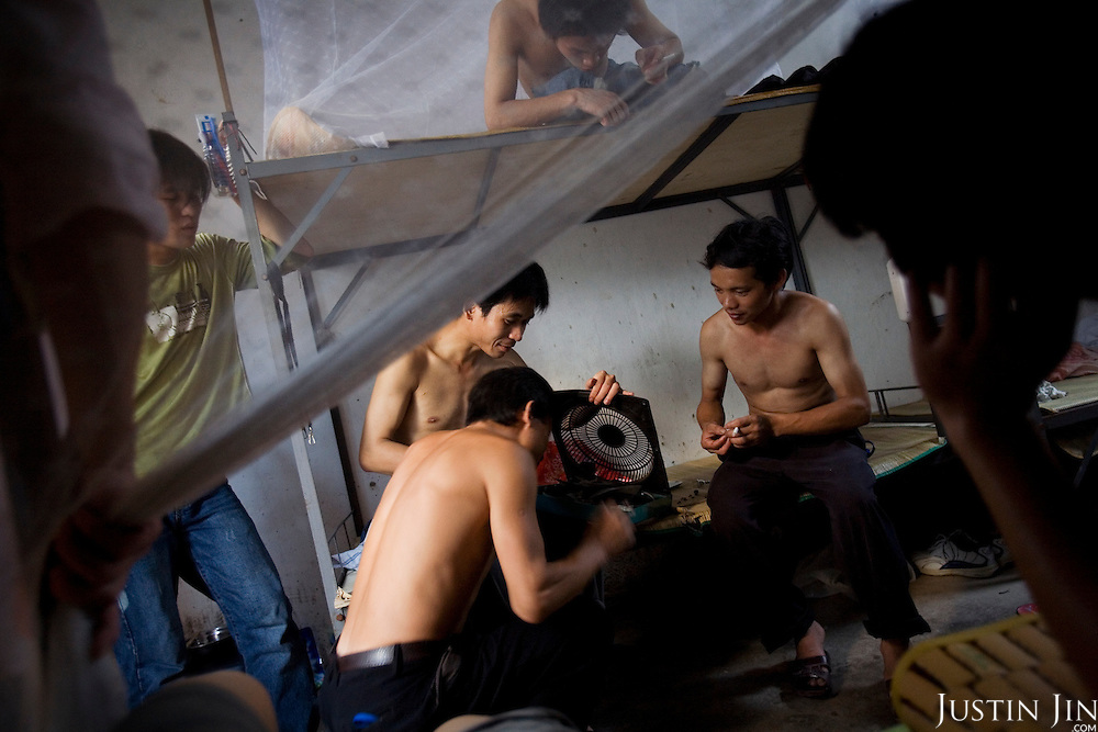 "Jeans workers fix a fan in their dormatory in Zhongshan city, China. .This picture is part of a photo and text story on blue jeans production in China by Justin Jin. .China, the ""factory of the world"", is now also the major producer for blue jeans. To meet production demand, thousands of workers sweat through the night scrubbing, spraying and tearing trousers to create their rugged look. .At dawn, workers bundle the garment off to another factory for packaging and shipping around the world..The workers are among the 200 million migrant labourers criss-crossing China.looking for a better life, at the same time building their country into a.mighty industrial power."