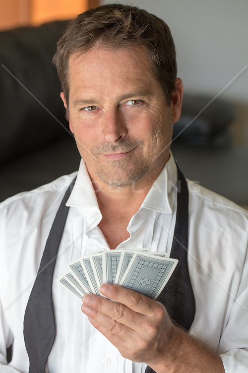 man in a tuxedo shirt and loose tie holding playing cards