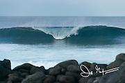 A wave breaks near a stone beach on North Seymour island, Galapagos, Ecuador.