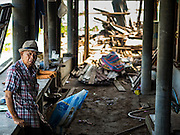 16 OCTOBER 2015 - BANGKOK, THAILAND:  A man being evicted from his home in the Wat Kalayanamit neighborhood sits in what used to be the walkway to his home. Fifty-four homes around Wat Kalayanamit, a historic Buddhist temple on the Chao Phraya River in the Thonburi section of Bangkok, are being razed and the residents evicted to make way for new development at the temple. The abbot of the temple said he was evicting the residents, who have lived on the temple grounds for generations, because their homes are unsafe and because he wants to improve the temple grounds. The evictions are a part of a Bangkok trend, especially along the Chao Phraya River and BTS light rail lines. Low income people are being evicted from their long time homes to make way for urban renewal.   PHOTO BY JACK KURTZ
