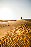 A lone woman walking bare foot on sand dunes in the Thar Desert of Rajasthan, India.