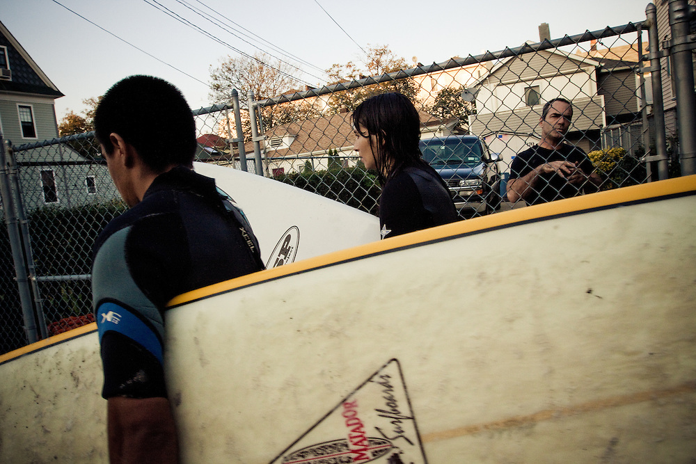 Salvador and Dara walk back to Boarders Surf Shop from Beach 91st Street surf break in Rockaway Beach, Queens, NY.