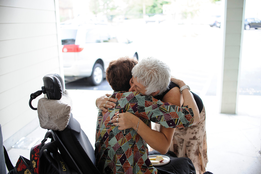 photo by Matt Roth..Takoma Village Cohousing resident Ann Zabaldo, who has multiple sclerosis, gets a goodbye hug from her friend Brigitte Wazana, a resident of the Blueberry Hill Cohousing community in Vienna, VA Saturday, September 22, 2012. Ann is a Principal Partner with Cohousing Collaborative, an organization which helps build cohousing complexes. She was involved in the development of TVC before anything was built.