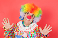 Portrait of funny clown with arms raised against colored background