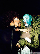 Two men wearing costume, one holding a fan, both sticking their tongues out at a club in Ibiza 1999.