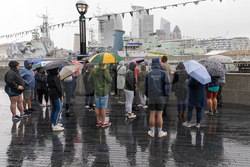 © Licensed to London News Pictures. 27/07/2019. London, UK. Tourists with umbrellas on a guided walking tour near the River Thames during heavy rain this morning. London and the UK are experiencing heavy rain and stormy weather today following the heatwave and record temperatures during the week. Photo credit: Vickie Flores/LNP