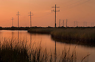 The sun sets on Grand Isle, a barrier island situated on the Gulf of Mexico at the southernmost tip of Louisiana, Nov. 23, 2010. The area was heavily affected when the Deepwater Horizon oil rig exploded April 20, 2010, killing 11 workers and causing the largest offshore oil spill in United States history. (Photo by Carmen K. Sisson/Cloudybright)