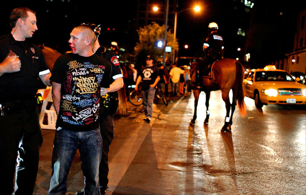 Xavier Mascareñas/Austin American-Statesman; Officer Christopher Kelly with the Austin Police Department questions a man who was hit by a bottle early July 11, 2008, as he is handcuffed following a fight Downtown. Officer Gary Shaw uses Reckless, a police horse, to keep the scene near Trinity Street and Seventh Street clear behind them.
