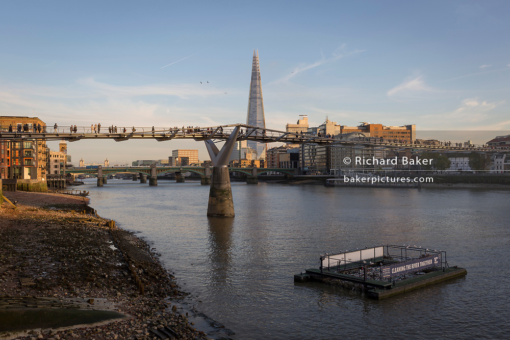 In late afternoon Autumn sunshine and with the tall point of the Shard skyscraper in the distance, gulls sit on one of the river litter cages on the Thames flowing beneath the Millennium Bridge, on 30th October 2017, in the City of London, England.