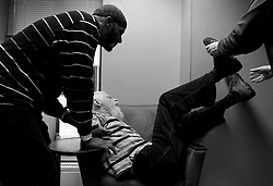 Caretaker Phillip Gant, left, and life partner David Schwartz, right, try to keep Stephen Lee calm whose body is moving uncontrolled while waiting inside the doctor's office. The traveling to a doctor's appointment agitates Stephen greatly and his movements, which he can't control because of his disease, are more intense.