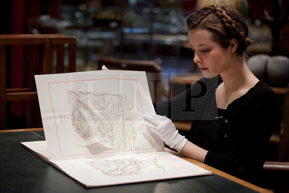 © Licensed to London News Pictures. 24/01/2013. London, UK. A Bonham's employee examines silk escape maps in an MI9 (the World War Two British  intelligence agency responsible for helping British prisoners of war to escape) catalogue from 1942 (est. GB£500-800) at the press view for the 'Bonham's Gentleman's Library Sale' in Knightsbridge, London, today (24/01/13). The sale, made up of weird, wonderful, rare and practical items, - all fit for a gentleman's library - is set to take place at 10am on the 24th of January at the auction house's Knightsbridge premises. Photo credit: Matt Cetti-Roberts/LNP