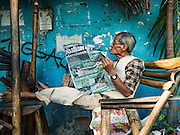 30 DECEMBER 2015 - BANGKOK, THAILAND:  A man reads a Thai newspaper in an abandoned bar in Bang Chak Market. The market is supposed to close permanently on Dec 31, 2015. The Bang Chak Market serves the community around Sois 91-97 on Sukhumvit Road in the Bangkok suburbs. About half of the market has been torn down. Bangkok city authorities put up notices in late November that the market would be closed by January 1, 2016 and redevelopment would start shortly after that. Market vendors said condominiums are being built on the land.           PHOTO BY JACK KURTZ