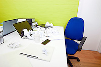 Crumpled paper over laptop on desk with empty chair and folders