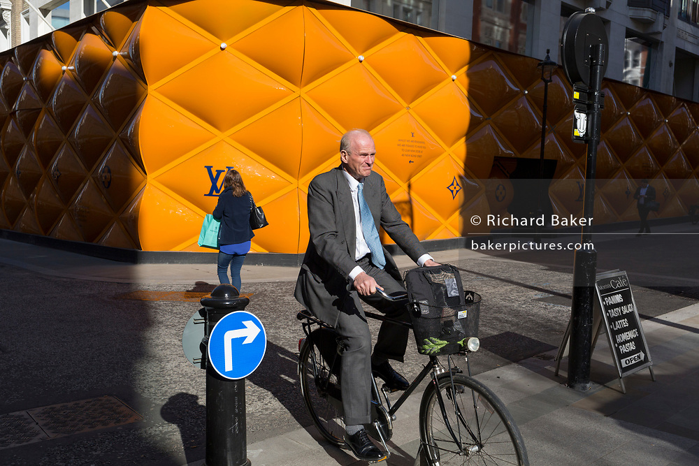 A middle-aged gentleman cycles past the temporary renovation hoarding of luxury brand Louis Vuitton in New Bond Street, on 25th February 2019, in London, England.