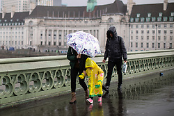 © Licensed to London News Pictures. 04/04/2019. London, UK. A family walk across Westminster Bridge as heavy rain falls in Westminster. Photo credit : Tom Nicholson/LNP