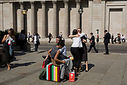 Two lady friends hug hello opposite the pillars of the Bank of England (right) at Bank triangle in the City of London, the capital's financial district (aka the Square Mile), on 22nd August 2019, in London, England.