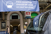 As the UK's Conornavirus pandemic lockdown continues, but with travel restrictions and social distancing rules starting to ease after three months of closures and isolation, a passenger walks beneath a large banner at Charing Cross station, advising the public to wear face coverings, a government requirement on all public transport from June 15th next week, on 9th June 2020, in London, England.