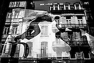 June 2015. Brussels. buildings reflected on a shop's window with a poster.