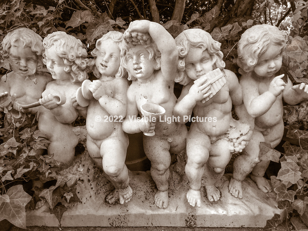 A sculpture of six cherubs in a traditional garden with ivy.