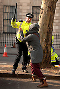 01/02/2009 A woman is threatened by a police officer as protesters at the Chinese Embassy attempt to attack the Chinese Premier Wen Jai Boa, as his car arrives there as part of a visit to London