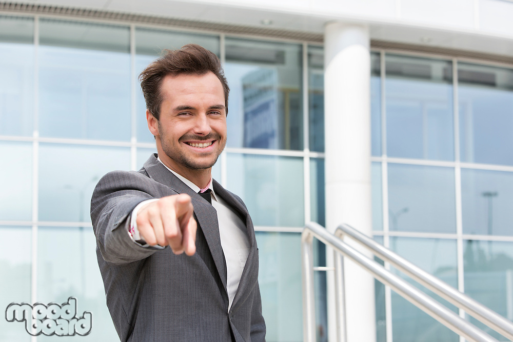 Portrait of happy businessman pointing at you outside office building