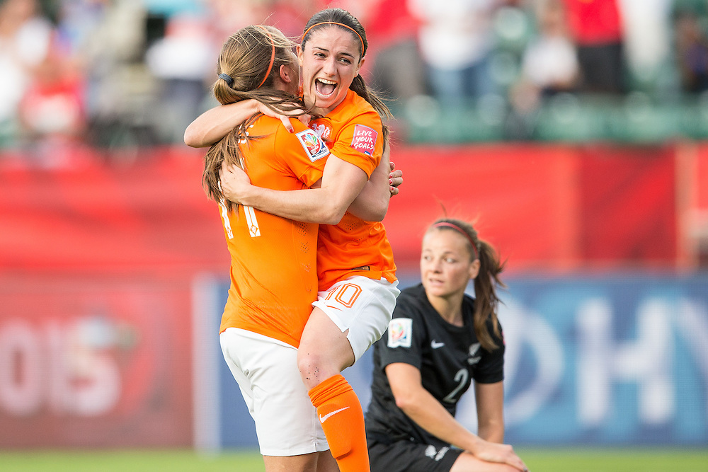 The Netherlands'  Lieke Martens (L) celebrates her goal with teammate Danielle Van De Donk during the first half of their Group A football match against New Zealand at Commonwealth Stadium on the opening day of the FIFA Women World Cup in Edmonton, Canada, June 6, 2015.   AFP PHOTO/GEOFF ROBINS