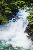 A man kayaking down a series of small waterfalls, Snoqualmie River (south fork), Washington, USA. Fall in the wall area.