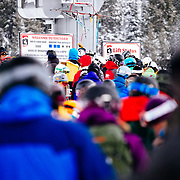 Skiers wait on line at the Thunder chair as a lone skier hits the pole chimes.