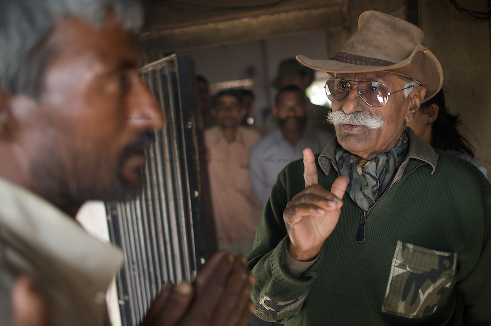 Fateh Singh of Tiger Watch (in hat) counsels Dasarath Mogia at the Faludi Forest Department range office on the edge of Ranthambore National Park. Dasarath, an ex-poacher who handed himself into forest officials, had just spent his first night in custody. Singh, with colleague Dharmendra Khandal, had paid Dasarath a visit to check on his well-being. It is alleged that Dasarath was beaten by forest guards during his first night in custody. Tiger Watch encourages poachers - many of them, including Dasarath, from the ostracised Mogia caste - to submit to the authorities by offering them and their families financial support and assistance with alternative livelihoods...Sariska National Park in Rajasthan was once home to dozens of tigers but by 2005 poaching had resulted in their complete eradication. Recognising the urgent need for intervention, the Indian and Rajasthan-state governments began the reintroduction of tigers into Sariska. Two cats were airlifted 200 km from Ranthambore National Park in June 2008. On November 5th an attempt to relocate a third tiger was postponed until later in the month. This relocation strategy is certainly an important part of the tiger conservation effort but many, including those like Dharmendra Khandal of the NGO Tiger Watch, argue that it will never be entirely successful without properly confronting the three essential issues that threaten tiger populations: poaching, habitat loss and the hunting of prey-base animals. In turn, these three issues cannot be addressed without acknowledging the malign influence of caste, poverty and poor administrative accountability. Poaching is almost exclusively undertaken by extremely poor and marginalised groups, including the Mogia caste who, without education, land and access to credit have limited alternative means of income. Many in the Mogia community also hunt bush meat for both their own consumption and to sell to others. This results in a depletion of the prey-base upon which tigers feed. E