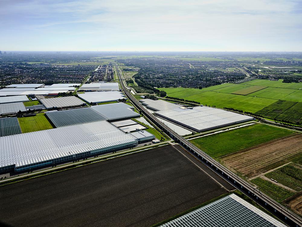 Nederland, Zuid-Holland, Bleiswijk, 14-09-2019; hogesnelheidslijn HSL doorsnijdt het kassengebied van Bleiswijk in de Overbuurtsche Polder. Skyline Rotterdam in het verschiet.<br /> The rails of the HST between the greenhouses of the vegetables and fruit producers in the west of the Netherlands, skyline Rotterdam<br /> <br /> luchtfoto (toeslag op standard tarieven);<br /> aerial photo (additional fee required);<br /> copyright foto/photo Siebe Swart