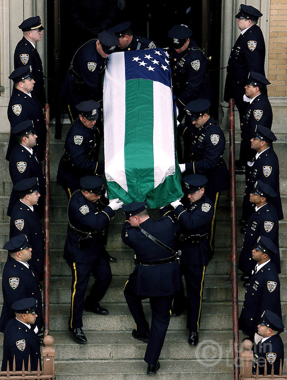 epa00596312 Police officers carry the casket of slain New York Police Officer Daniel Enchautegui down the steps of St. John's Chrysostom Church following his funeral mass Wednesday 14 December 2005 in the Bronx, New York. Enchautegui, 28, was shot Saturday when he confronted two men who police say were attempting to break into the house next door to his own home. He is the second police officer to die in the line of duty this year, both killings took place within the last two weeks.  EPA/JUSTIN LANE