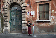 A restaurant worker takes a smoke break at a plaza in downtown Rome